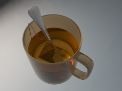 Glass with tea, tea bag and spoon.